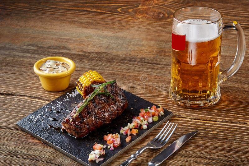 Roastbeef arrostito della bistecca del filetto e salsa di funghi sul tagliere nero e vetro di birra su fondo di legno fotografia stock libera da diritti