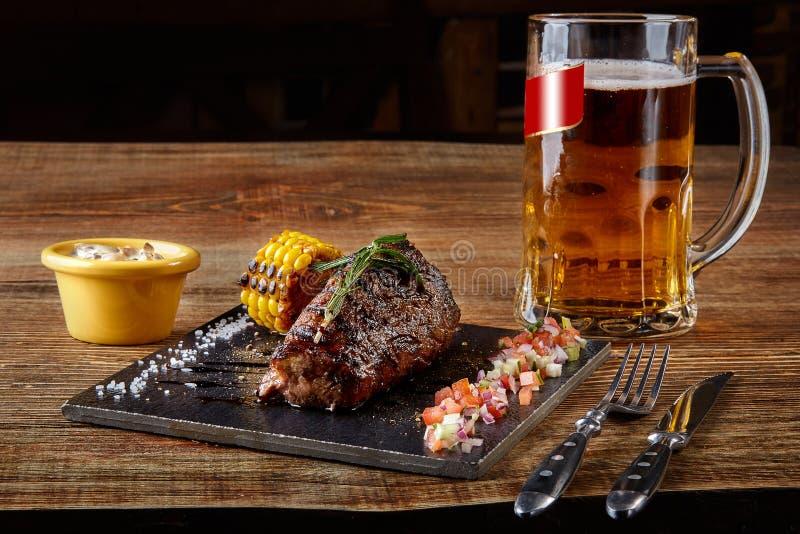 Roastbeef del filete del filete y salsa de setas en tabla de cortar negra y vidrio asados a la parrilla de cerveza en la tabla de imagenes de archivo