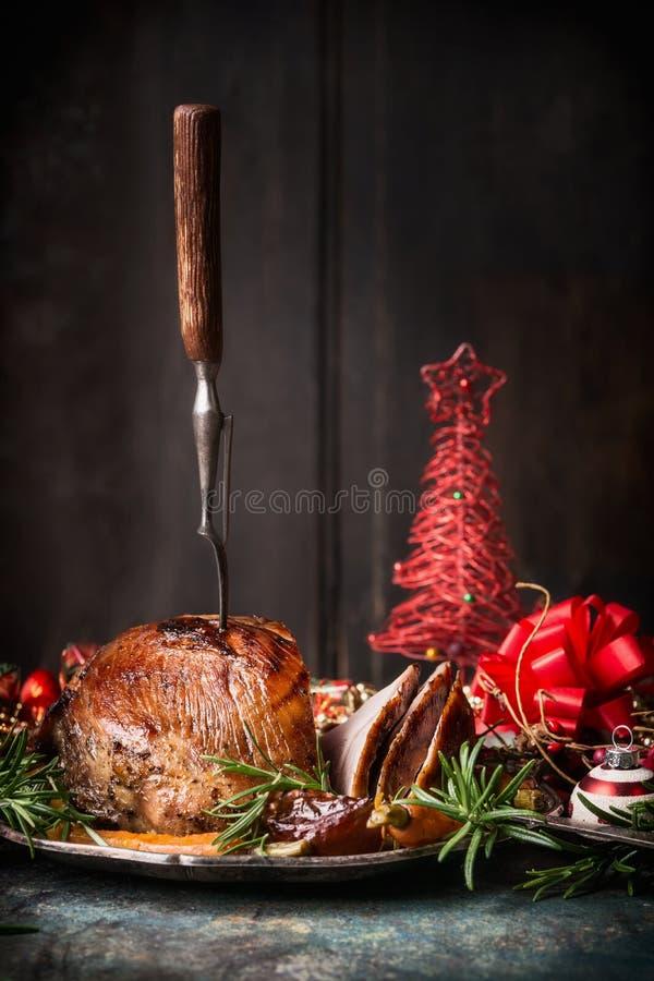 Roasted切了与叉子的圣诞节火腿和红色欢乐假日装饰在黑暗的木背景 免版税图库摄影