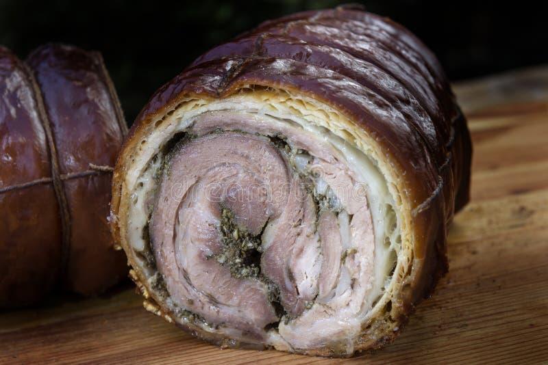 Roasted свернуло отрезок свинины в половине на прерывая доске стоковое фото