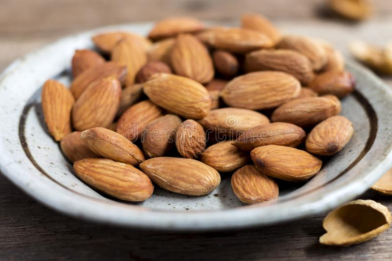 Roasted almonds, salt in dish of green on a wood table. Almonds are rich in nutrients, vitamins and minerals that are essential to. The body stock images