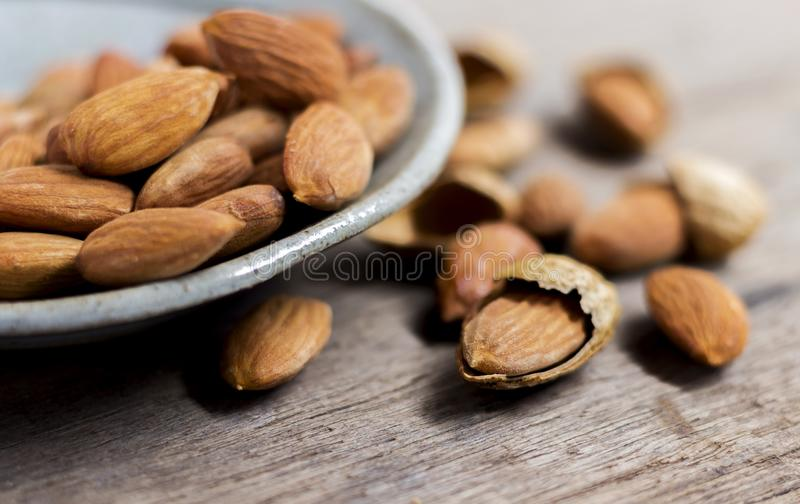 Roasted almonds, salt in dish of green on a wood table. Almonds are rich in nutrients, vitamins and minerals that are essential to. The body royalty free stock photography