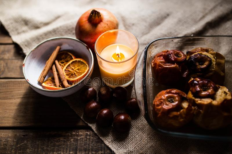 Roasted apples in a glass tray with chestnuts, cinnamon, orange and pomegranate stock image