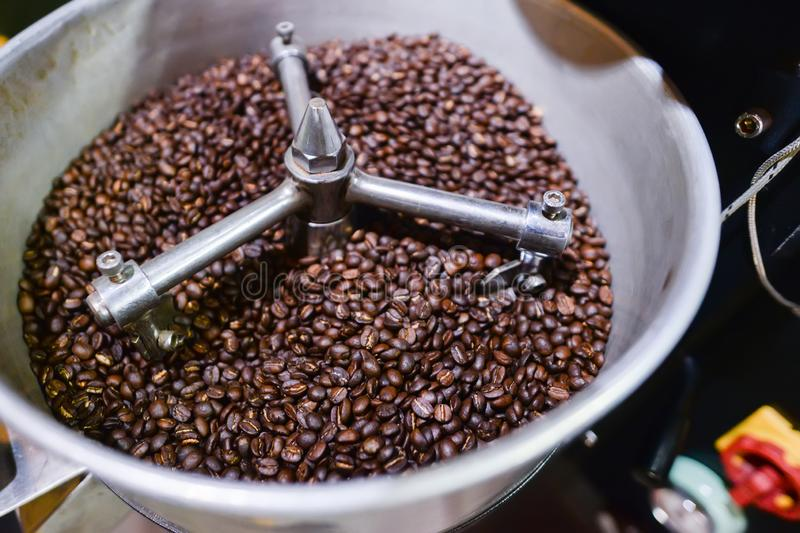 Roasted arabica coffee beans process in roasted coffee machine in coffee industry stock photography