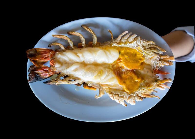Roasted asó a la parrilla el camarón o la gamba gigante del río en la placa azul, comida tailandesa del estilo en el fondo negro imagen de archivo