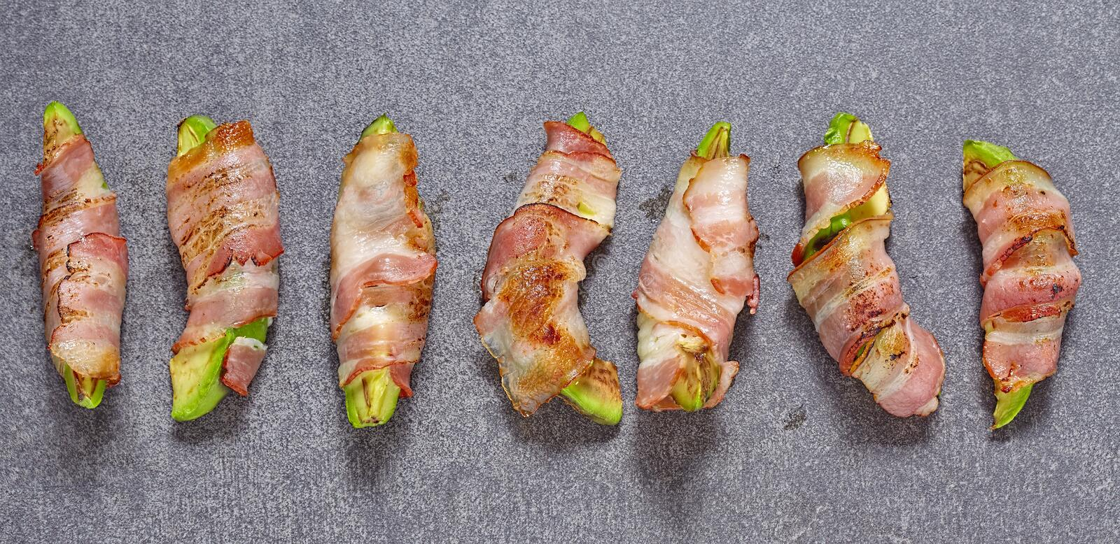 Roasted avocado pieces wrapped in bacon. Ketogenic diet royalty free stock photos