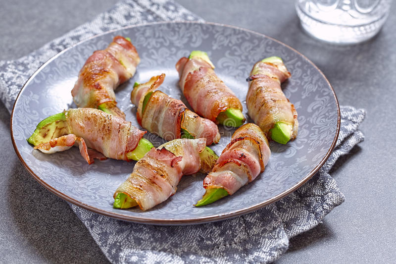 Roasted avocado pieces wrapped in bacon. Ketogenic diet royalty free stock photo