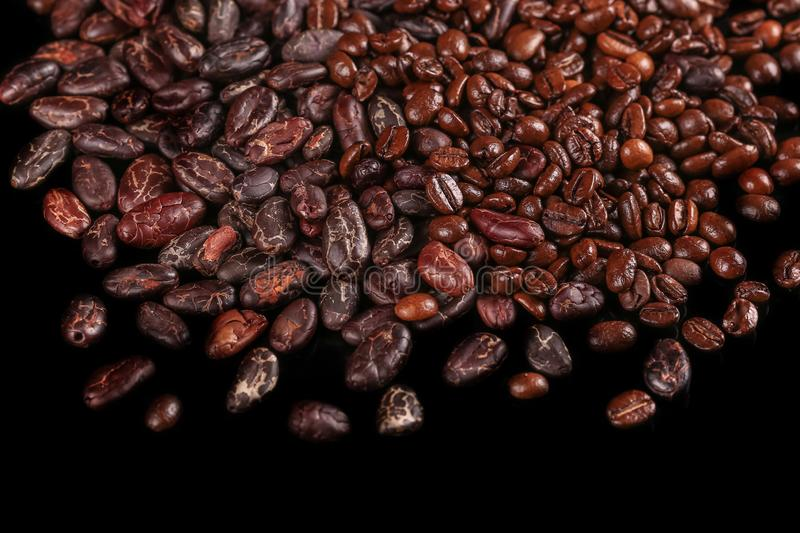 Roasted beans. Cocoa beans and coffee beans. Roasted beans. Cocoa beans and coffee beans isolated on black background stock photo