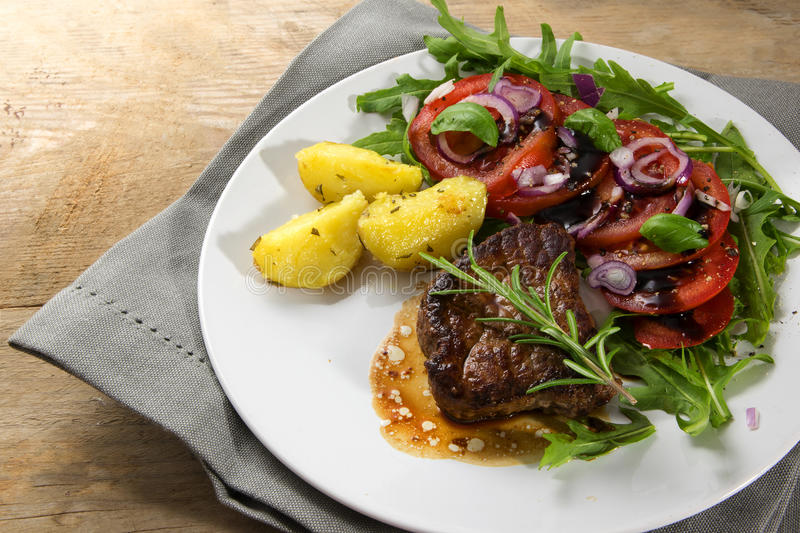 Roasted beef filet mignon with potatoes and tomato arugula salad. On a white plate on a rustic wooden board royalty free stock images