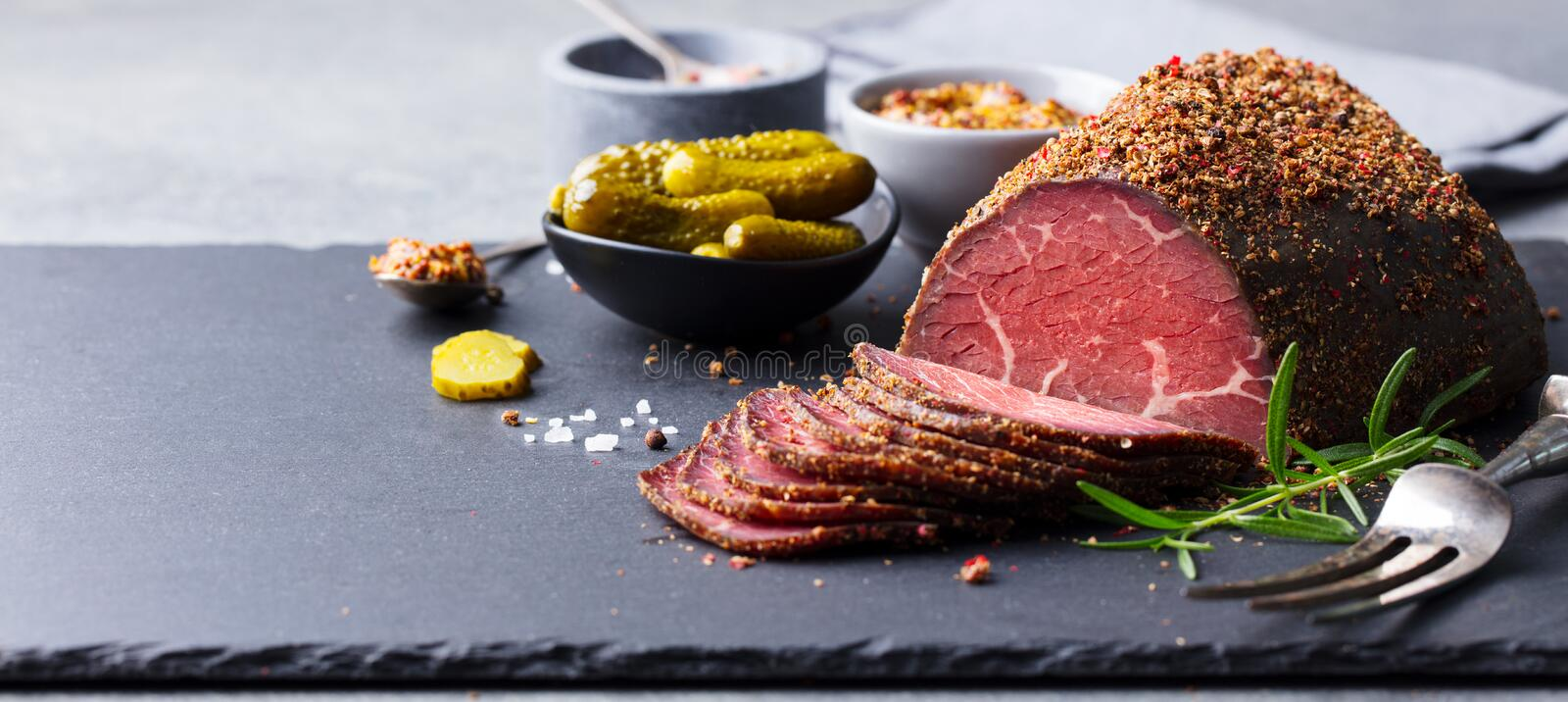 Roasted beef, pastrami on slate cutting board. Copy space stock images