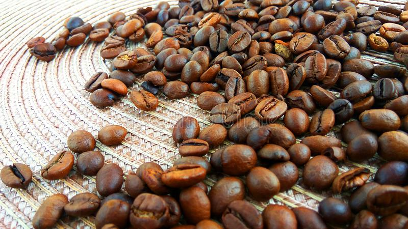 Roasted brown coffee beans on light textile cloth background. Close up roasted brown coffee beans on light textile cloth background royalty free stock photo