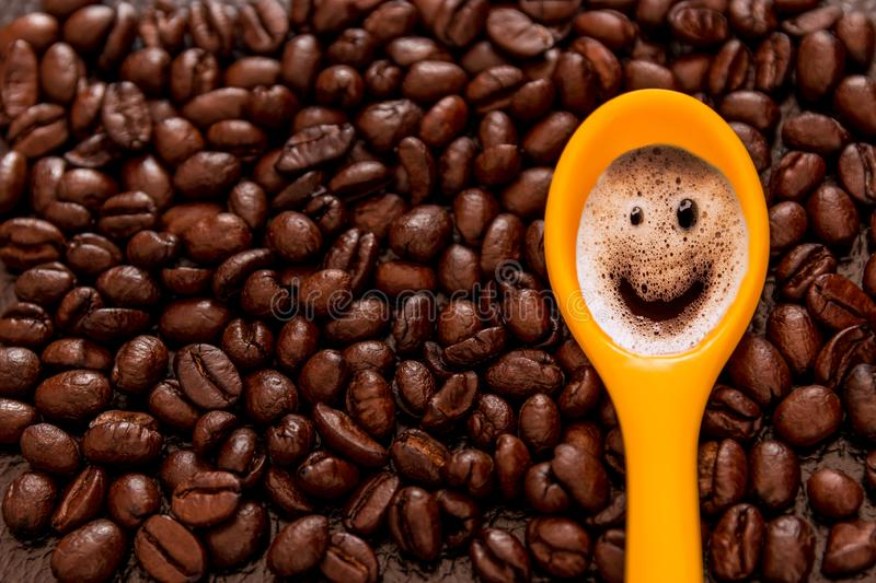 Roasted brown coffee beans pattern, background, top view and smiley face yellow spoon stock image