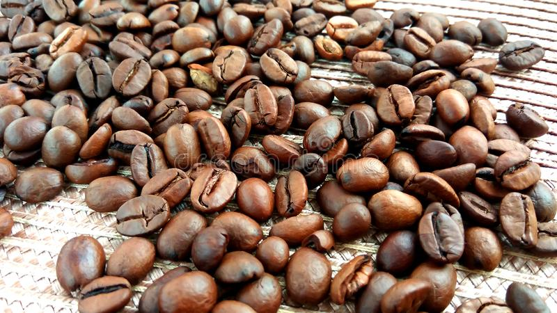 Roasted brown coffee beans on textile cloth background. Roasted brown coffee beans on cloth background stock photos