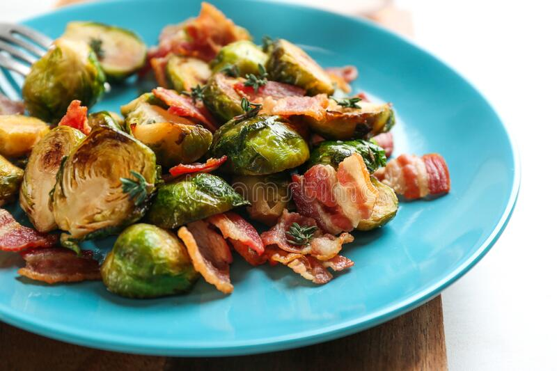 Roasted brussels sprouts with bacon on plate. Closeup stock photos