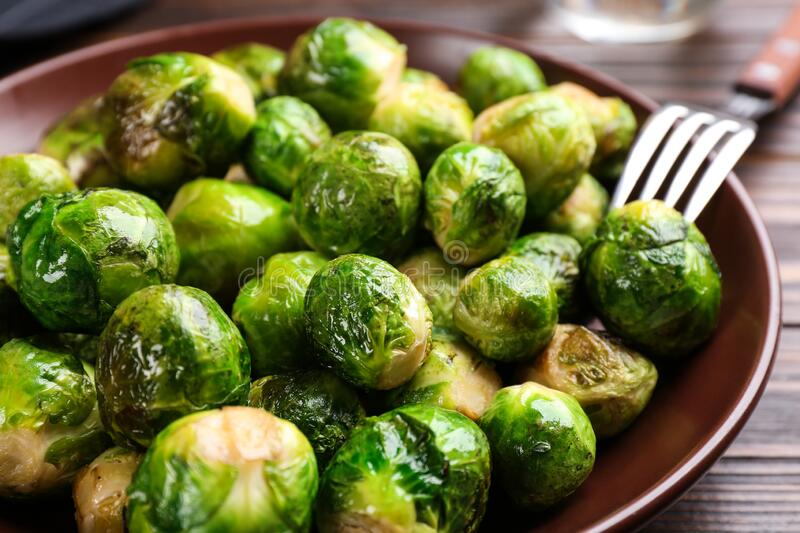 Roasted Brussels sprouts in plate on table. Closeup stock photography