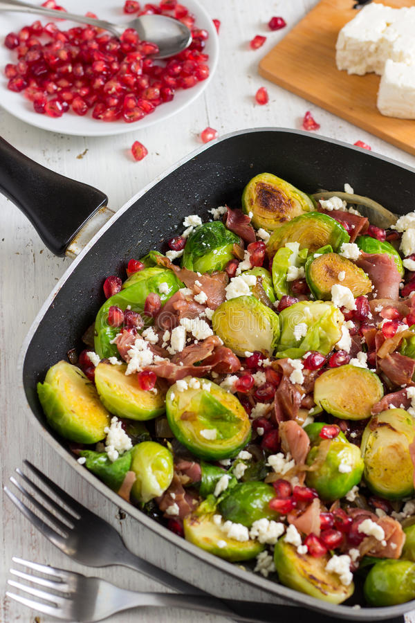 Roasted Brussels Sprouts Salad. Tasty roasted Brussels sprouts salad with prosciutto, pomegranate and Feta cheese stock photos