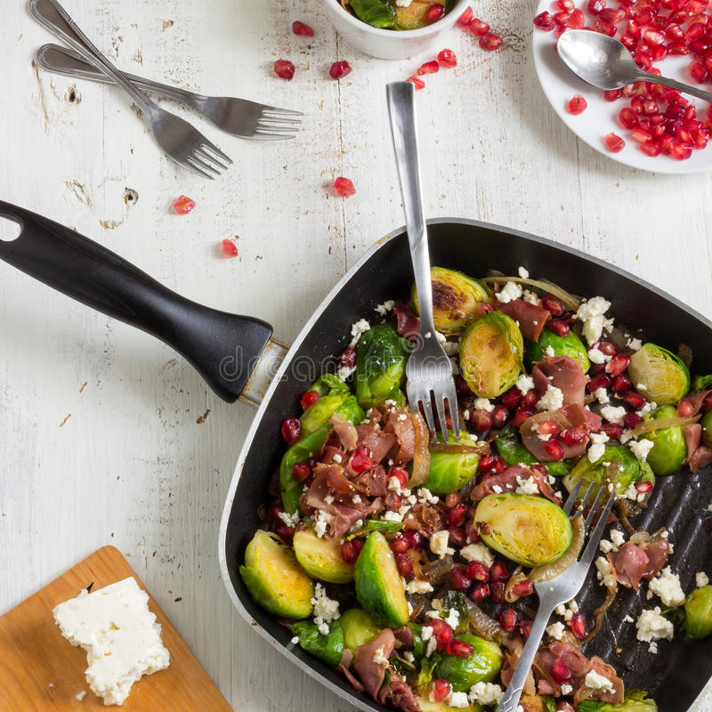 Roasted Brussels Sprouts Salad. Tasty roasted Brussels sprouts salad with prosciutto, pomegranate and Feta cheese stock images