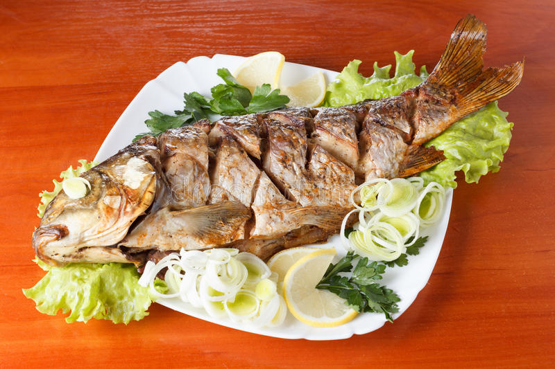 Roasted carp fish with vegetables entirely. Traditional Christmas meal. stock photography