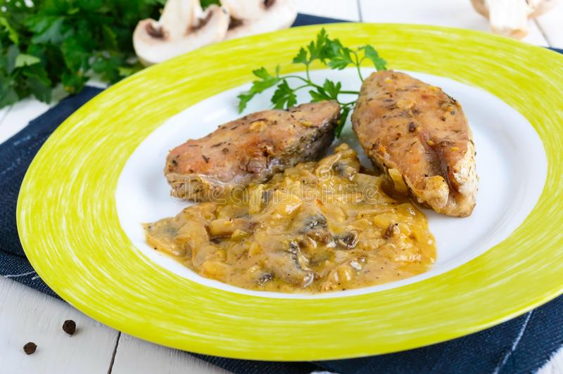 Roasted carp steaks with mushroom sauce on a plate on a white wooden background. stock photography