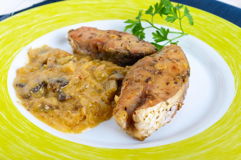 Roasted carp steaks with mushroom sauce on a plate on a white wooden background. stock photos