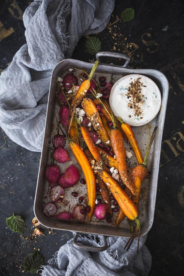 Roasted Carrots, Roasted Radishes with Dukkah Spice and Feta Cheese Sauce. On wood backgrund royalty free stock images