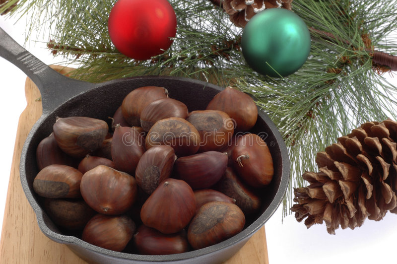 Roasted Chestnuts. Pan of freshly roasted chestnuts and a pine bough stock images
