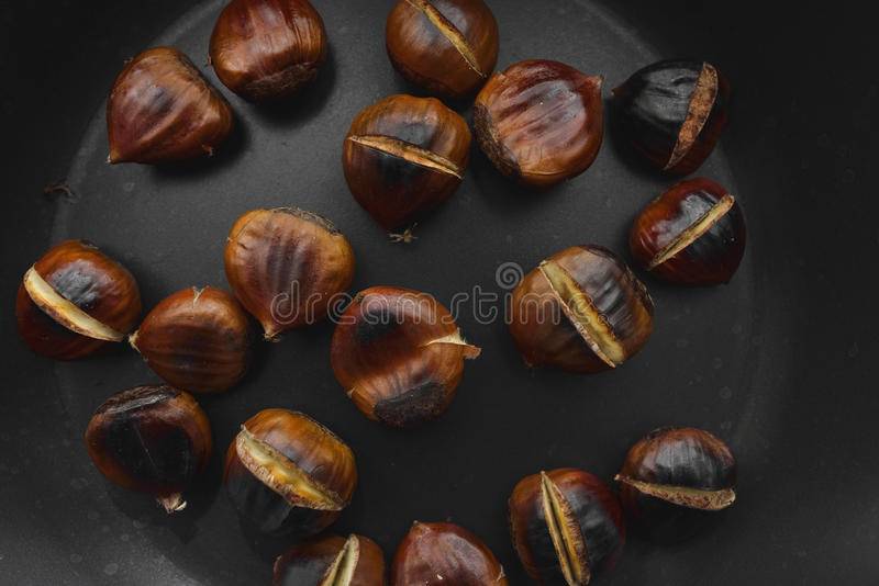 Roasted chestnuts in a cast iron skillet on a wooden table stock photo