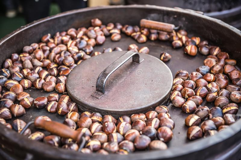 Roasted chestnuts in a frying pan somewhere in the street market.  royalty free stock image