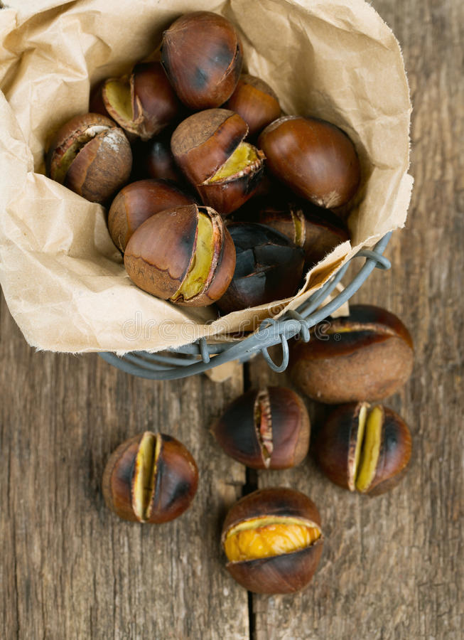 Roasted chestnuts on wooden surface royalty free stock photos