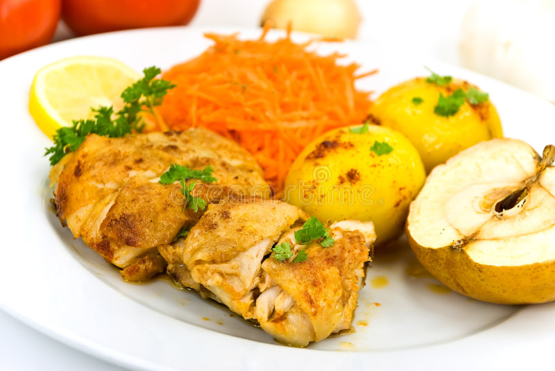 Roasted chicken with apple and fried potatoes stock image