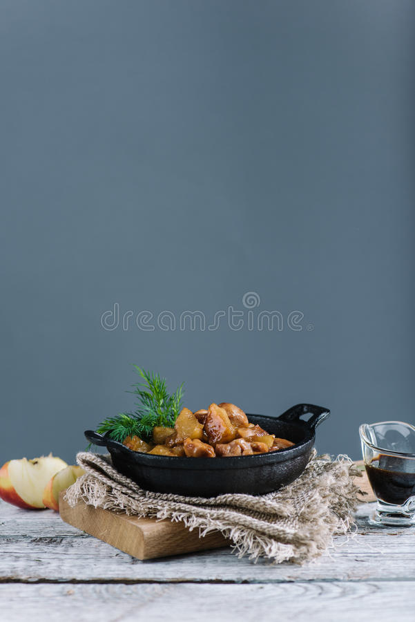 Roasted chicken with apples served with fresh dill in black iron pan, copy space. Homemade roasted chicken with apples served with fresh dill in black iron pan royalty free stock image