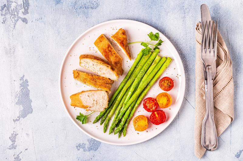 Roasted chicken breast with asparagus and tomatoes stock photos