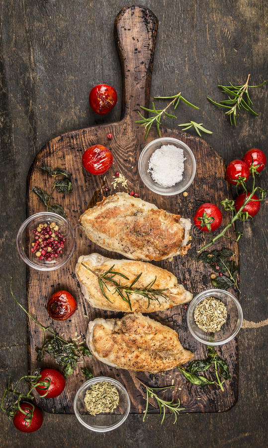 Roasted chicken breast with fried herbs and tomatoes on rustic cutting board, top view stock images