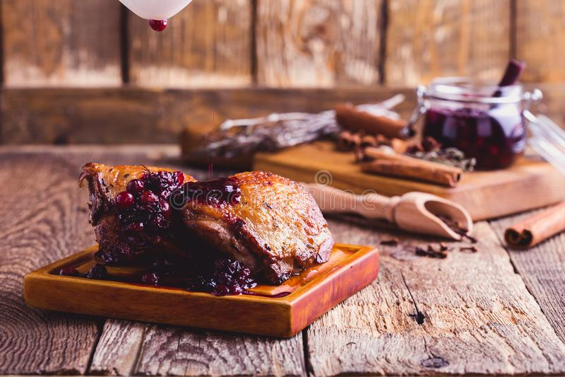 Roasted chicken. Cranberry sauce pouring over chicken legs stock photography