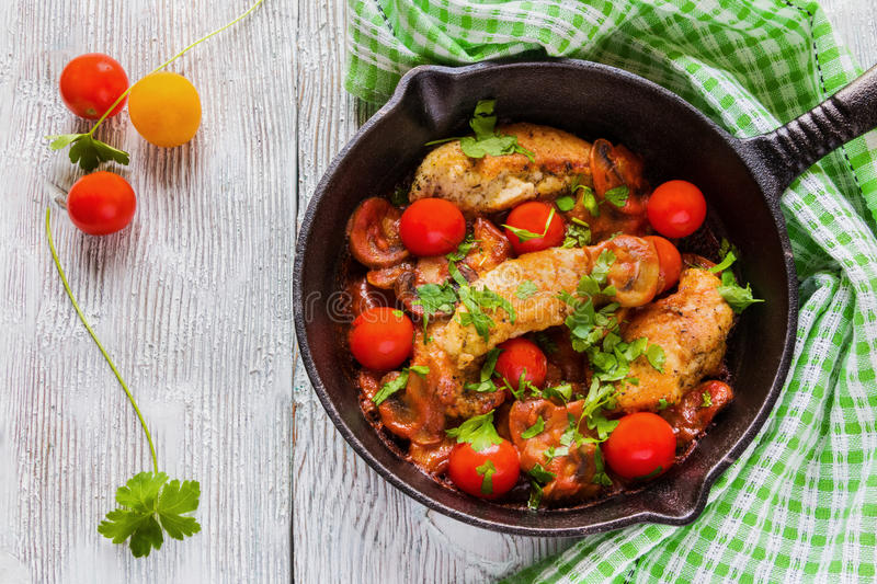 Roasted chicken fillet, cooked with mushrooms, garlic, paprika and olive oil. Cast-iron skillet and fresh cherry tomatoes on royalty free stock photo