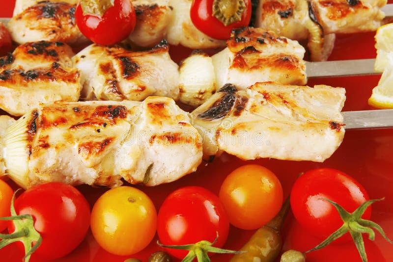 Roasted chicken kebab on red. Fresh roast chicken shish kebab on red platter royalty free stock image