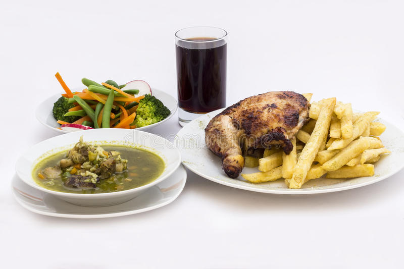 Roasted chicken leg with fries potato called Pollo a la Brasa. Menu served with fresh salad, chicken soup of coriander stock photography