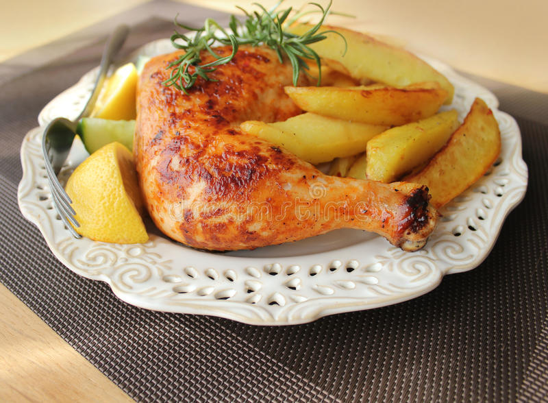 Roasted chicken leg with fries potato and lemon royalty free stock image