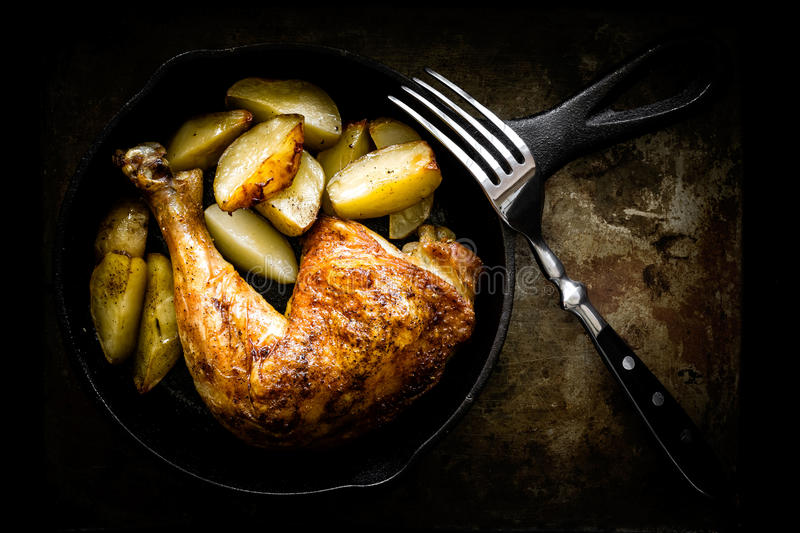 Roasted chicken leg with potatoes royalty free stock photos