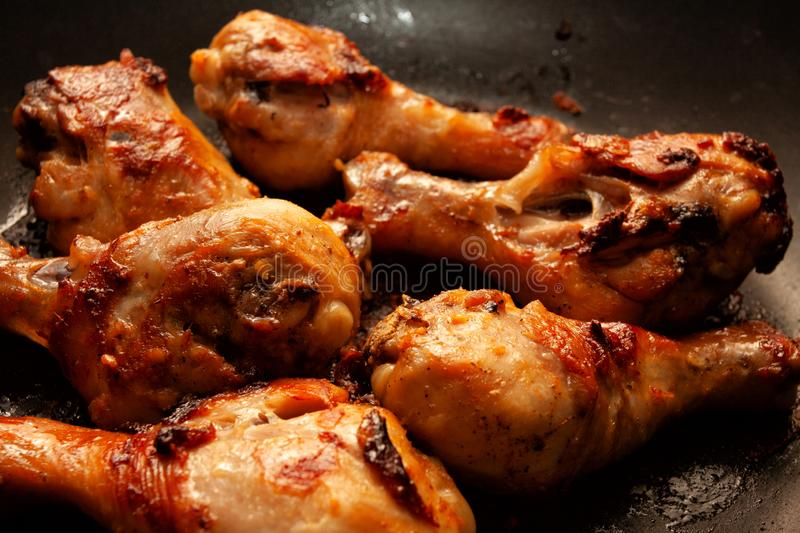 Roasted chicken legs in a black pan. Roasted chicken legs in a pan, alternatives, animal, appetizer, asia, baked, barbecue, bowl, bread, cilantro, cooked, course royalty free stock photo