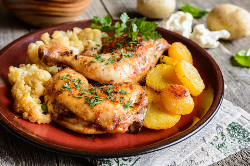Roasted chicken legs with potato and cauliflower. Roasted chicken legs garnished with potato and cauliflower stock photography