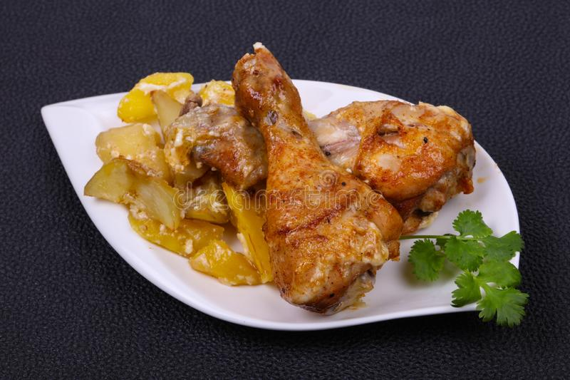 Roasted chicken legs with potato royalty free stock image
