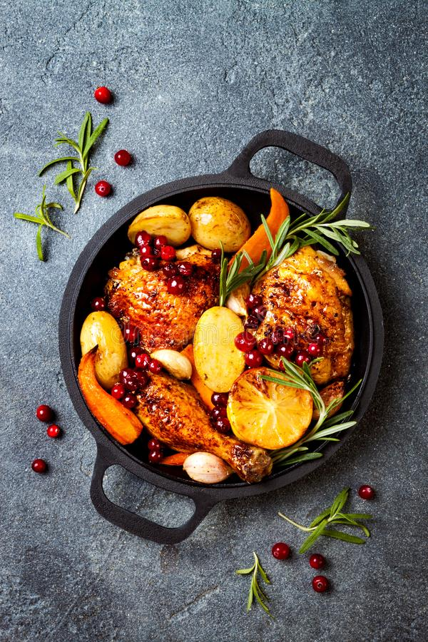 Roasted chicken legs with root vegetables, lemon, garlic, cranberry and rosemary on pan stock images