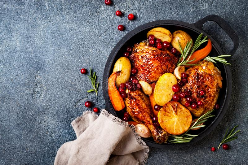 Roasted chicken legs with root vegetables, lemon, garlic, cranberry and rosemary on pan. On black slate stone background stock image