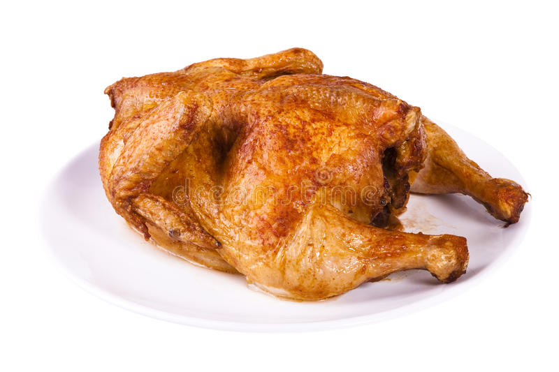 Roasted chicken on plate. Golden roasted chicken on white plate isolated on a white background royalty free stock image