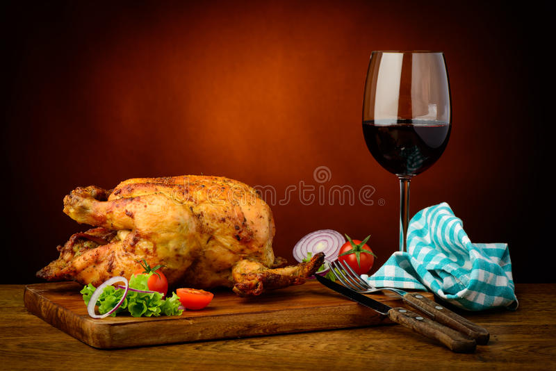Roasted chicken and red wine. Still life with traditional roasted chicken and red wine stock photo