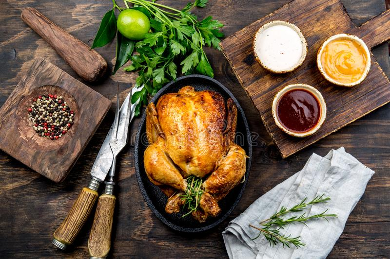 Roasted chicken with rosemary served on black plate with sauces on wooden table, top view. royalty free stock photos