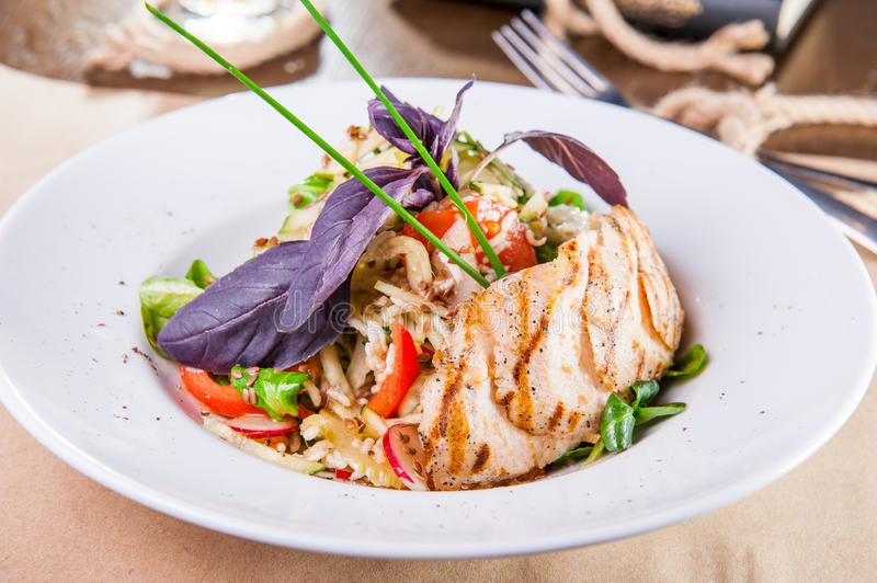 Roasted chicken salad with greenery and vegetables on the white plate. Selective focus, copy space royalty free stock photo