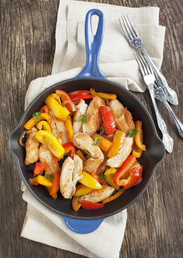 Roasted chicken with sweet peppers. In pan stock images