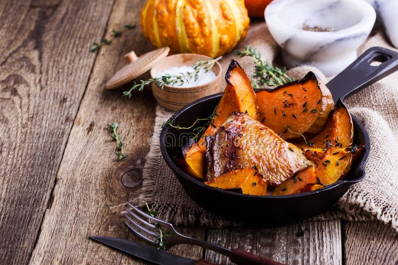 Roasted chicken thighs with sliced butternut squash pumpkin and. Fresh thyme in cast iron skillet on rustic wooden table, autumn or winter cozy dinner dish stock images